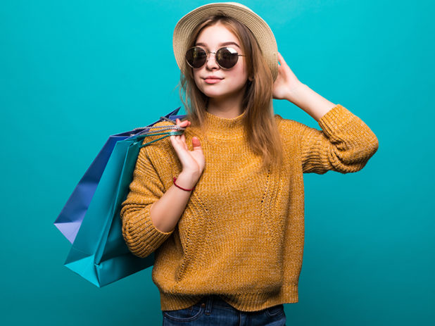 Young teen woman in sunglasses and hat holding shopping bags in her hands feeling so happiness isolated on green background